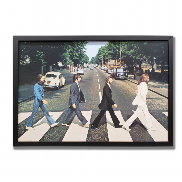 A large photo of The Beatles crossing Abbey Road crosswalk. The photo is surrounded by a black frame. The Beatles Poster Perth