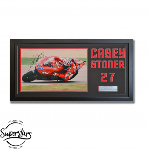Framed photo of Casey Stoner riding his bike. The photo is signed by Casey. It also has typography of his name and racing number.